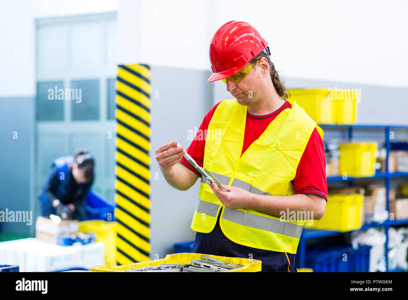 Manager in a factory checking a product from production line. Factory supervisor doing quality control - Stock Image