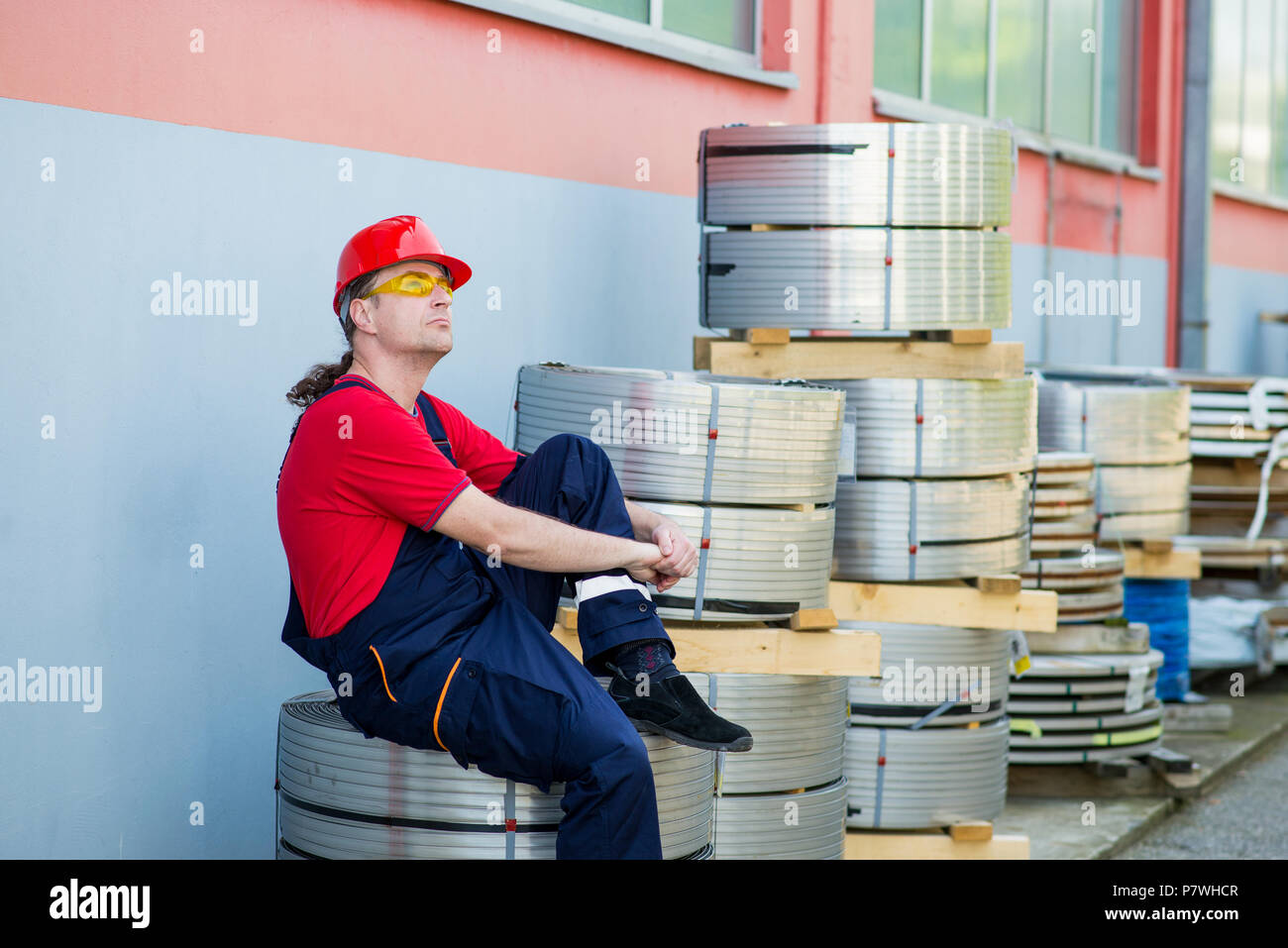 Factory worker with red helmet resting outside a factory - Stock Image