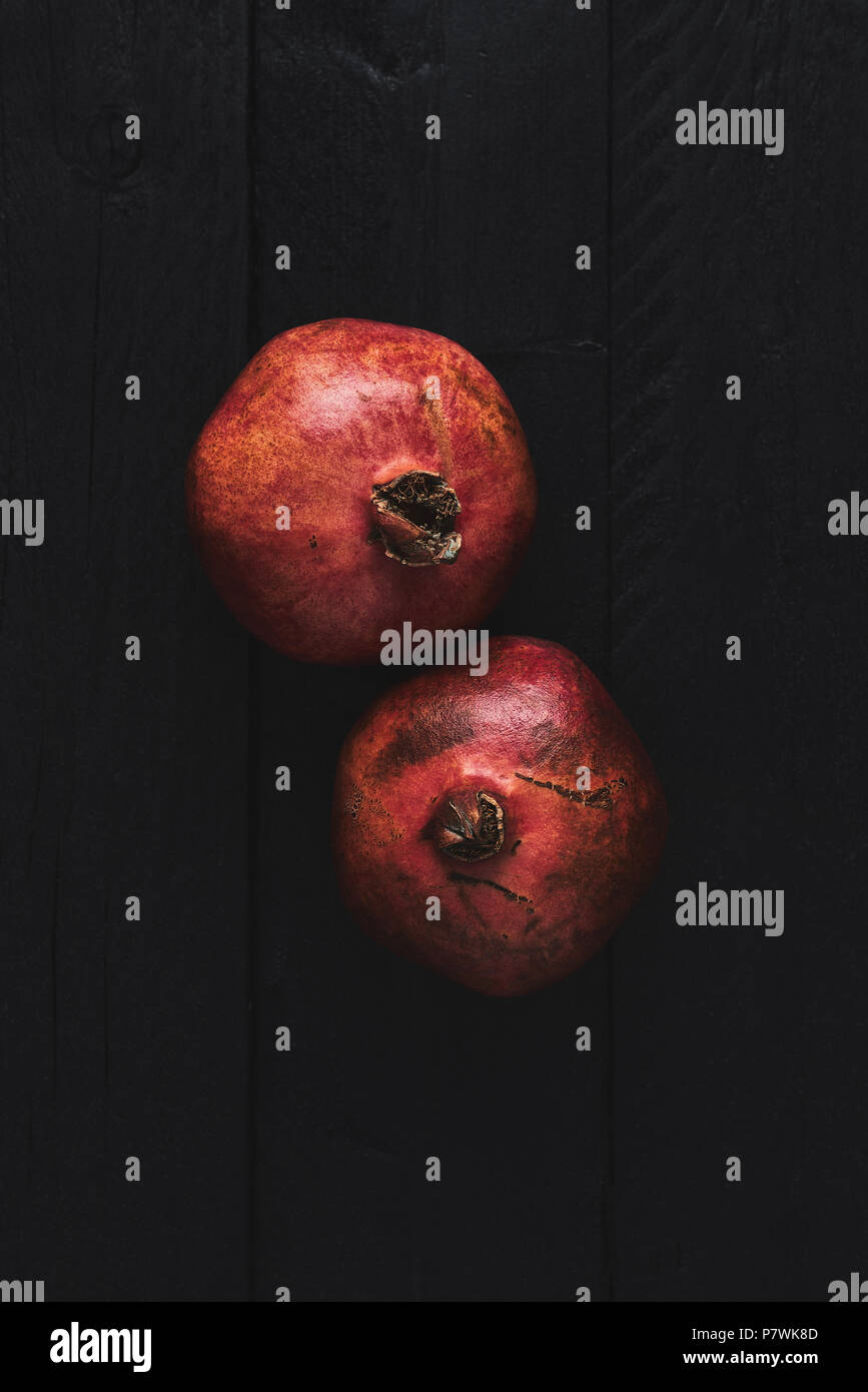 Flat lay of two ripe pomegranate fruit on black wooden vintage background. Top view with copy space. - Stock Image