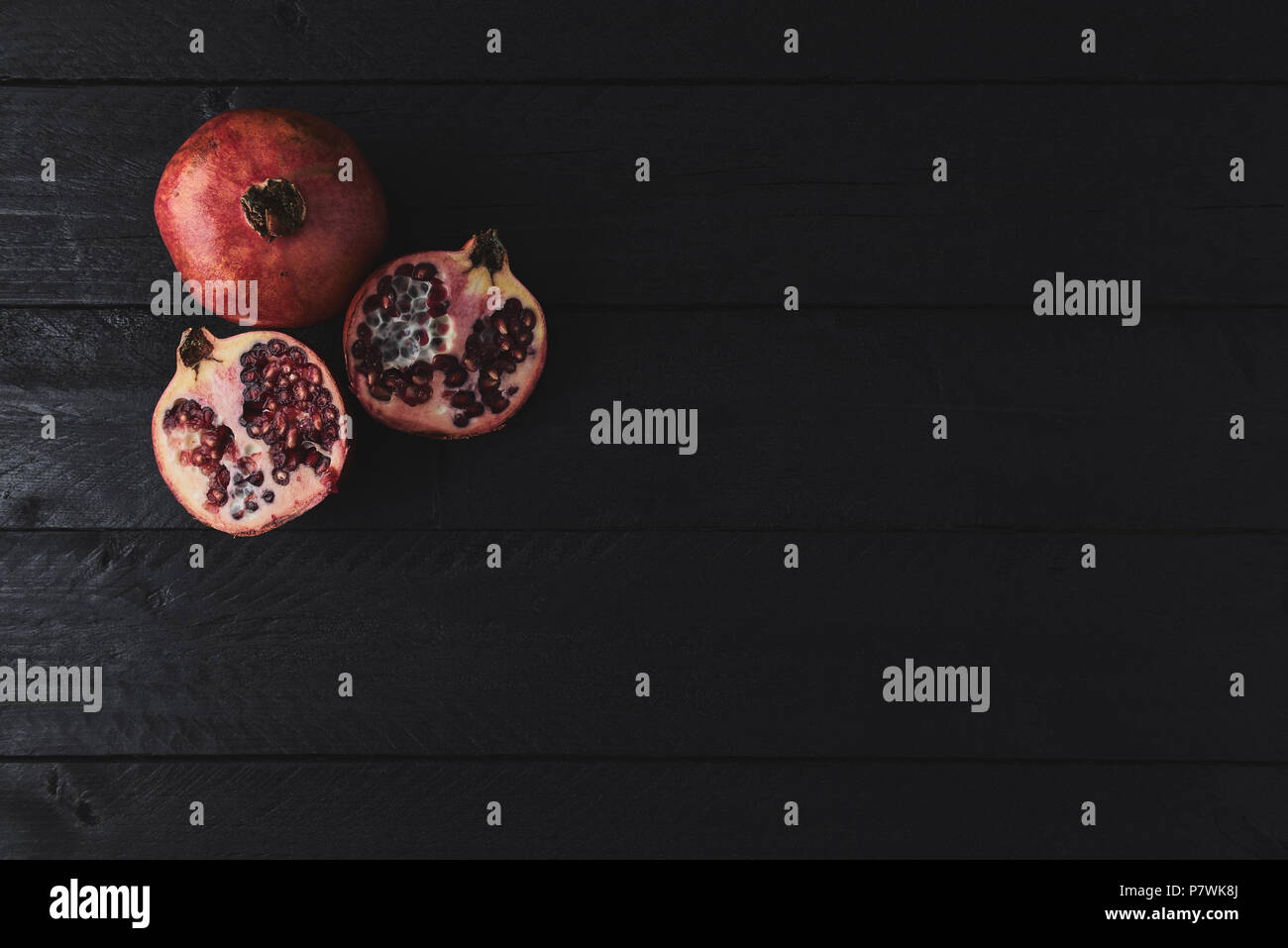 Flat lay of ripe pomegranate fruit on black wooden vintage background. Top view with copy space. Stock Photo