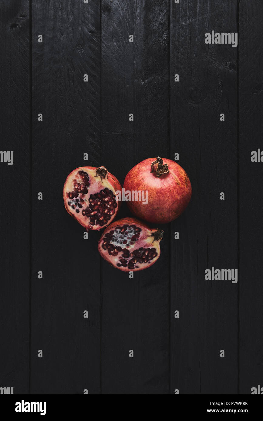 Flat lay of ripe pomegranate fruit on black wooden vintage background. Top view with copy space. - Stock Image