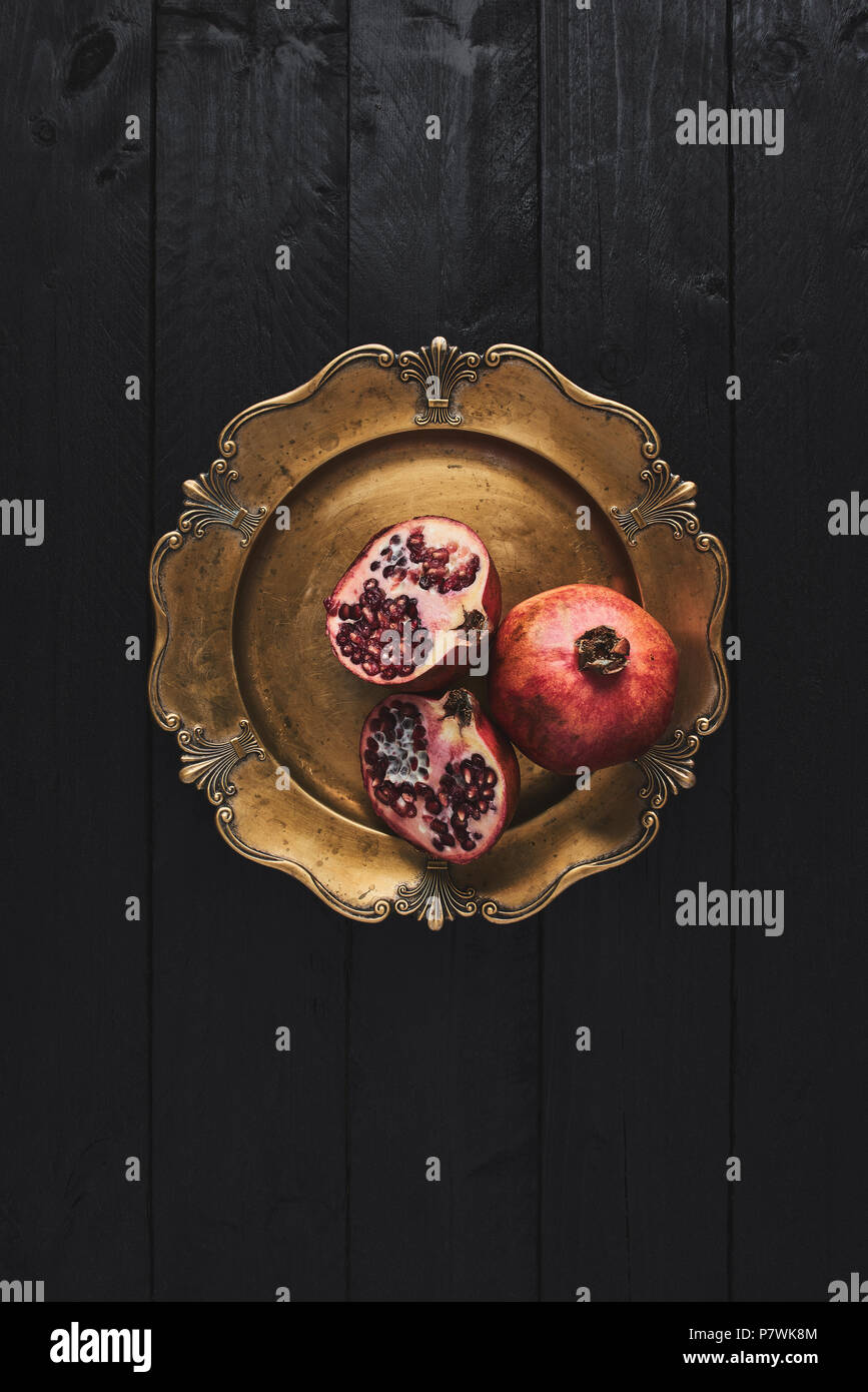 Flat lay of ripe pomegranate fruit on an old golden serving plate, black wooden vintage background. Top view with copy space. - Stock Image