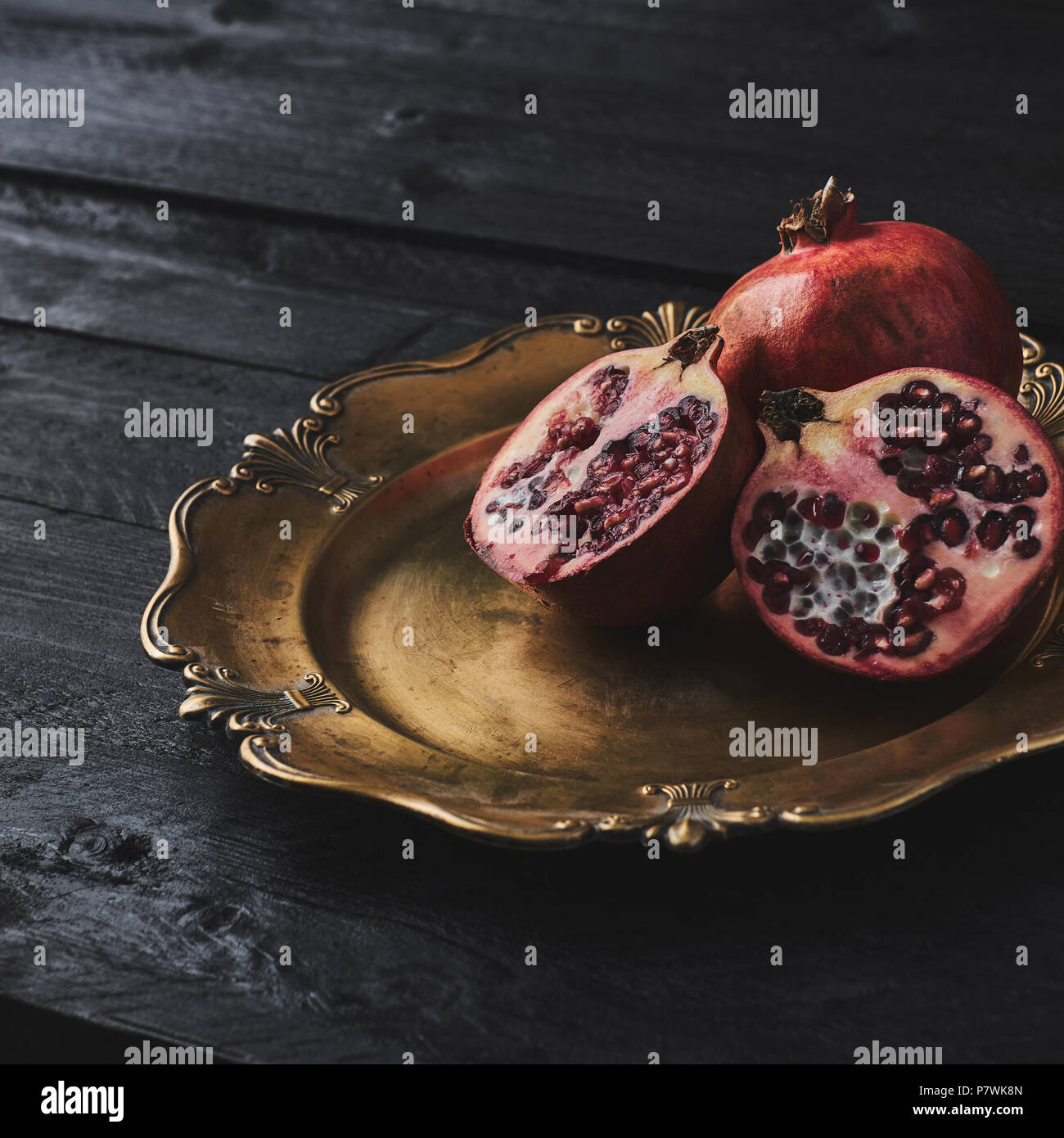 Ripe pomegranate fruit on an old golden serving plate, black wooden vintage background. Narrow depth of field, square crop, copy space. - Stock Image