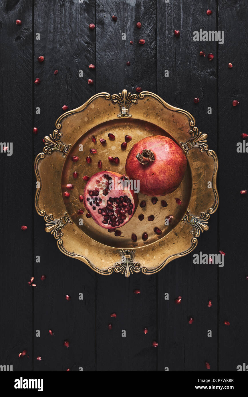 Flat lay of ripe pomegranate fruit surrounded by seeds on an old golden serving plate, black wooden vintage background. Top view with copy space. - Stock Image