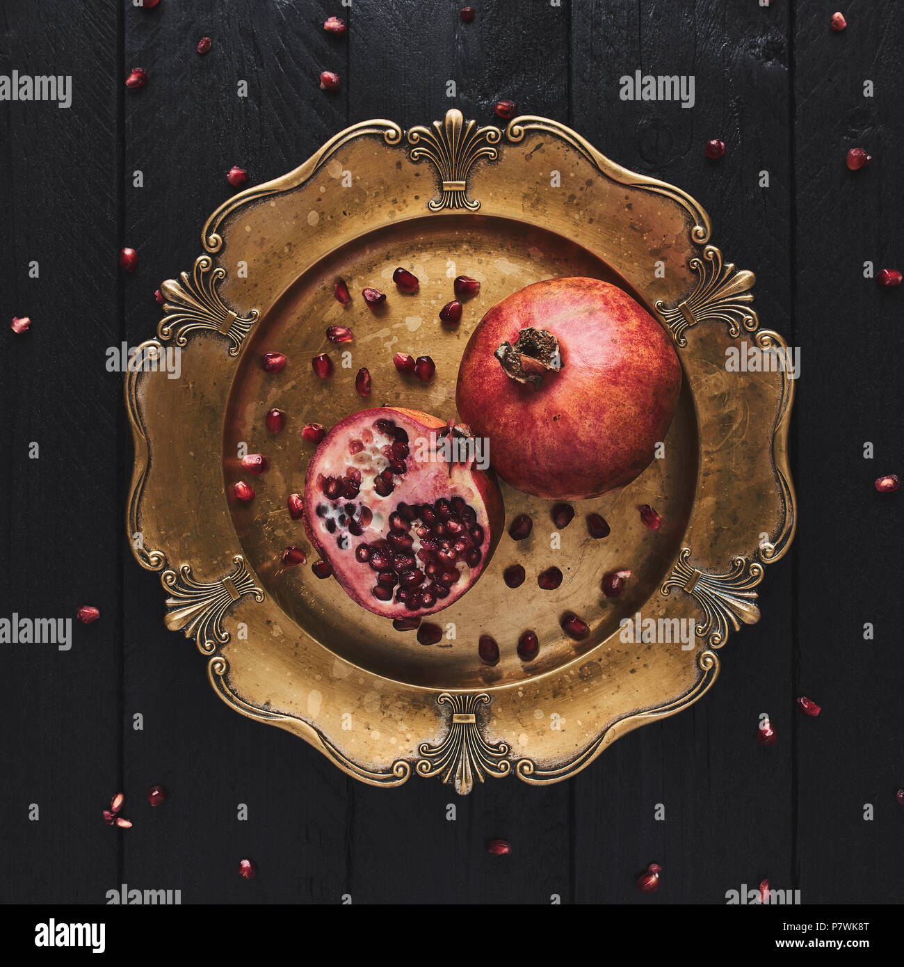 Flat lay of ripe pomegranate fruit surrounded by seeds on an old golden serving plate, black wooden vintage background. Top view, square crop. - Stock Image