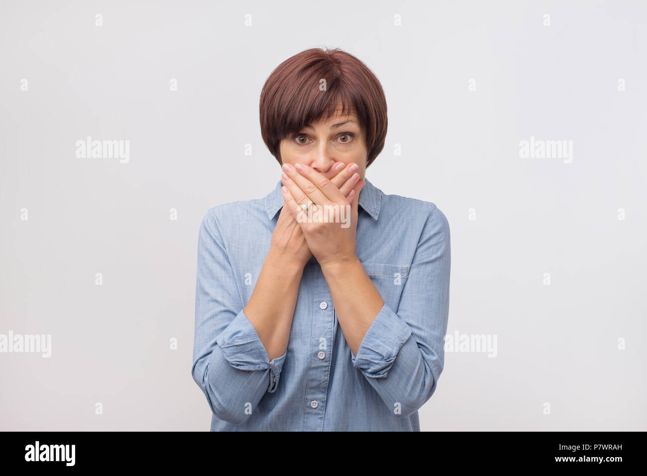 Close up portrait of attractive, mature woman in blue shirt closing her mouth with fingers. She is worried. - Stock Image