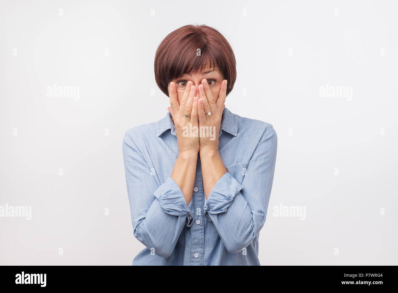 Close up portrait of attractive, mature woman in blue shirt closing her face with fingers. She is worried. - Stock Image