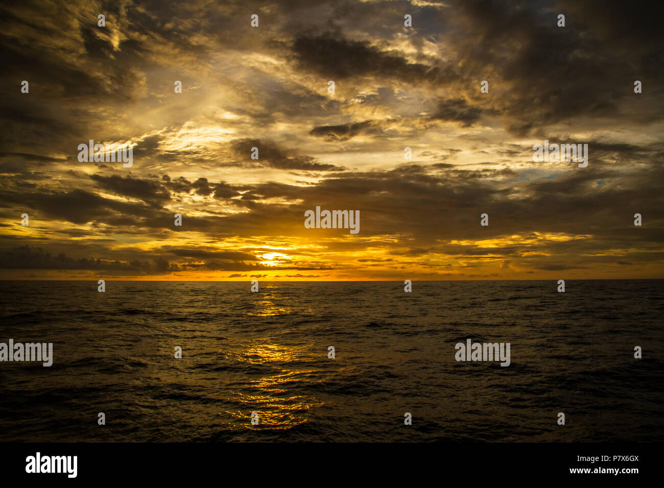 Beautiful sunset on the ocean with a dramatic cloud and golden sunset sky - Stock Image