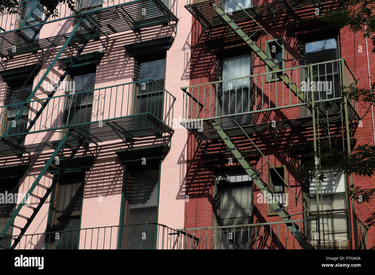 Close up of two old brick buildings in lower Manhattan painted pink and red, with green fire escapes that cast interesting shadows on their facades - Stock Image
