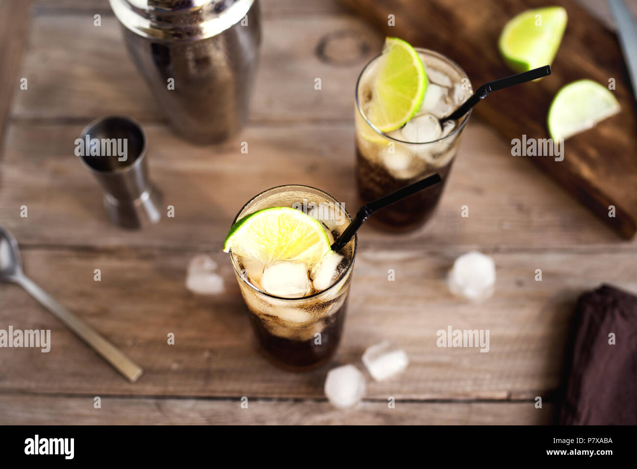 Rum and Cola Cuba Libre drink with lime and ice on rustic wooden table - Stock Image