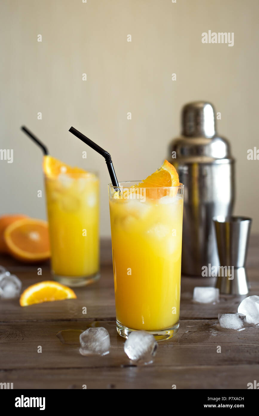 Screwdriver Cocktail with vodka, ice and orange juice. Homemade screwdriver cocktail drink on wooden table, copy space. - Stock Image