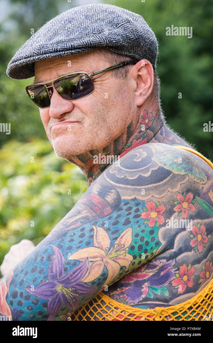 Middle aged man with Japanese flower pattern tattoos, England, UK - Stock Image