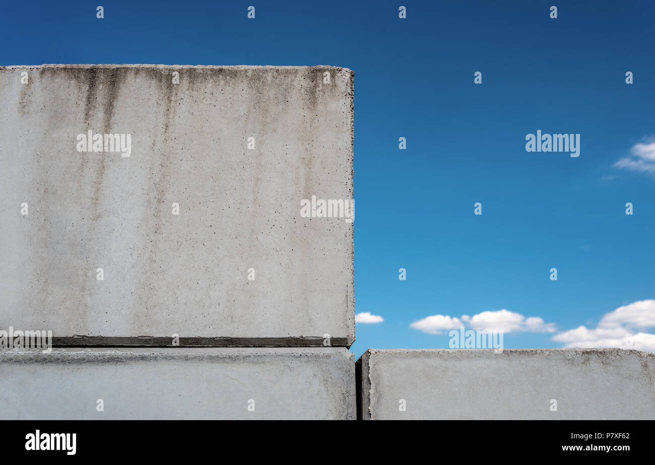 Detailed background of concrete wall photo texture on blue beautiful sky background with white clouds. - Stock Image