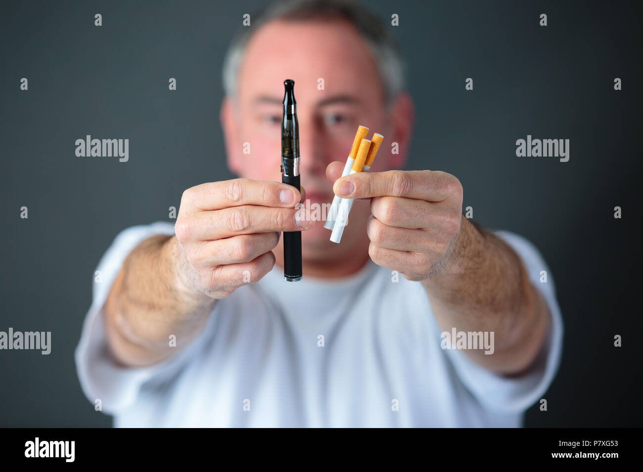 doctor comparing conventional tobacco cigarettes and electronic vaporizer - Stock Image