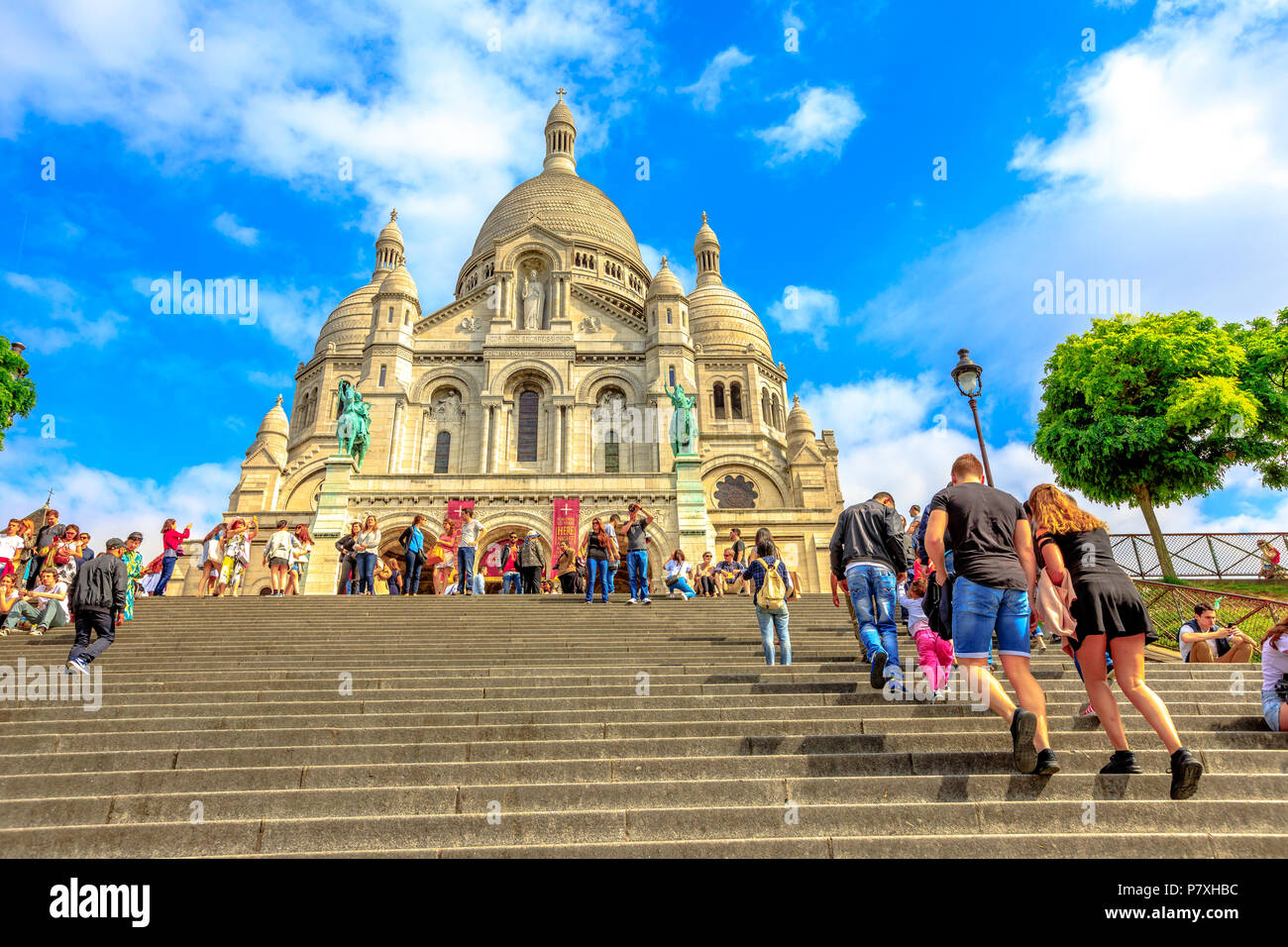 Paris, France - July 3, 2017: tourists climb up the steps leading to Basilica of Sacre Coeur de Montmartre in Paris in a sunny day with blue sky. Sacred Heart Church is a popular tourist landmark. - Stock Image