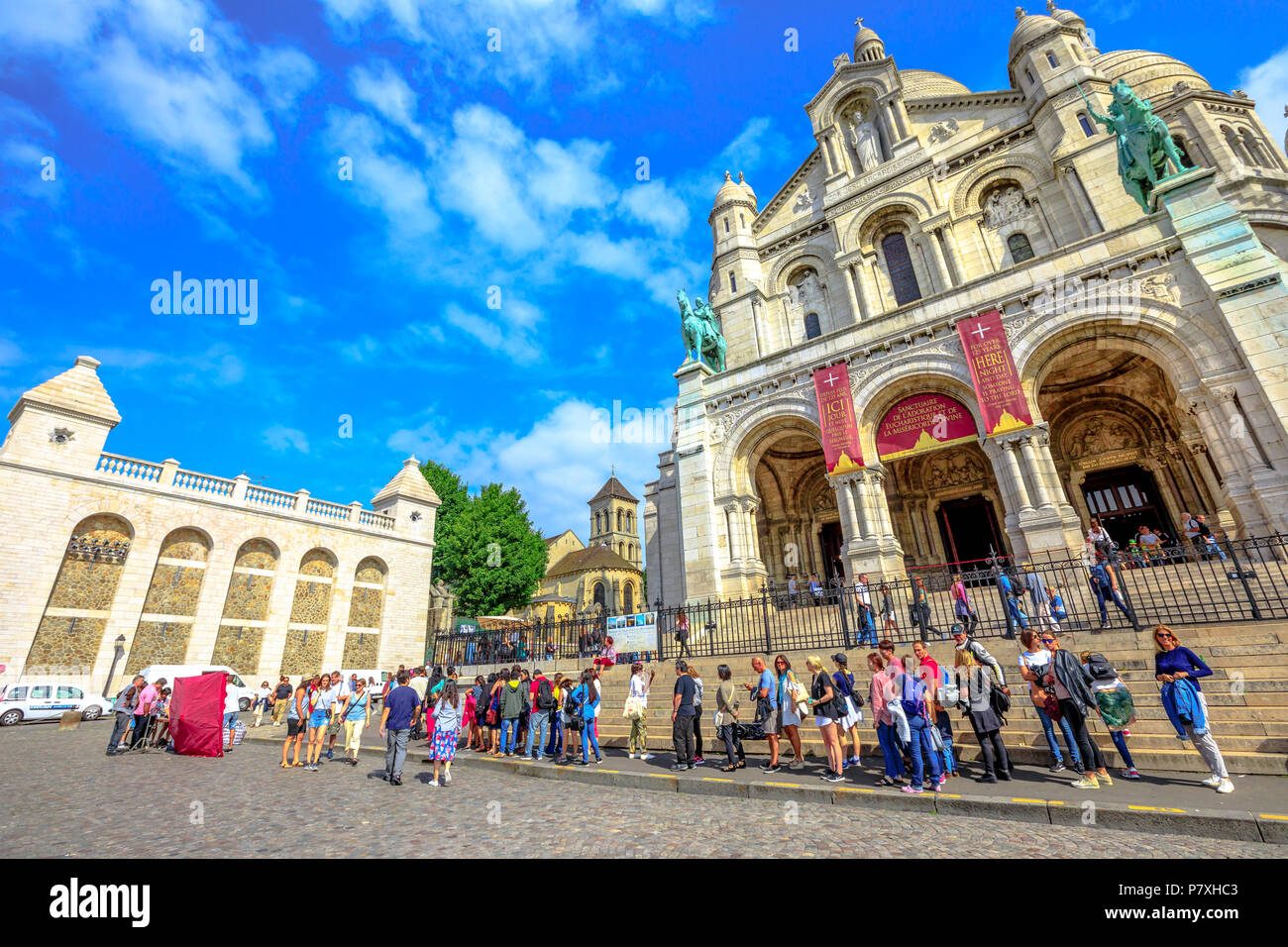 Paris, France - July 3, 2017: perspective view of people in front of Basilique du Sacre Coeur de Montmartre. Sacred Heart Church is a popular attraction and landmark in Paris. Sunny day blue sky. - Stock Image
