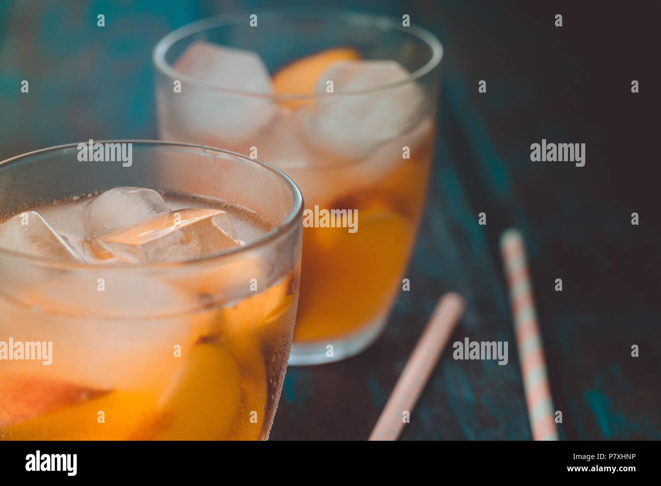 Peach aperol spritz with peach slices on wooden desk. Summer cocktails. Cold peach lemonade. - Stock Image