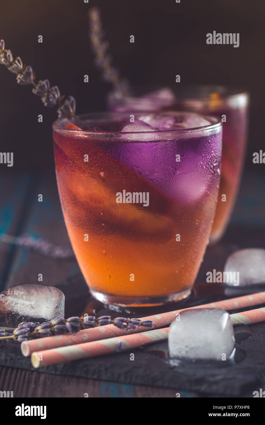 Peach aperol spritz with peach slices and lavender water on wooden desk. - Stock Image
