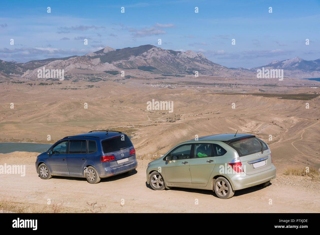 Volkswagen Sharan and Honda FR-V. The car is parked on a mountain Meganom near wind turbines. Republic of Crimea. October 30, 2015. - Stock Image