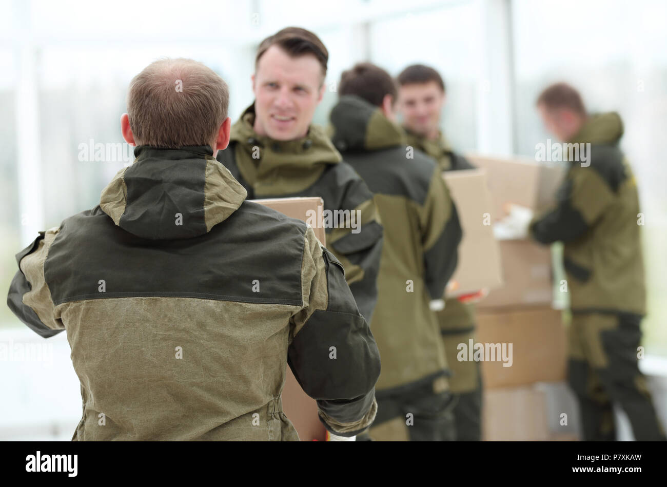 Happy male movers in uniform carrying boxes Stock Photo