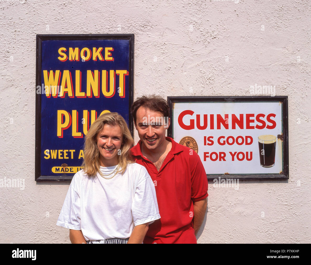 Couple by vintage tin-plate advertising signs, Bunratty Folk Park, Bunratty, County Clare, Munster Province, Republic of Ireland - Stock Image