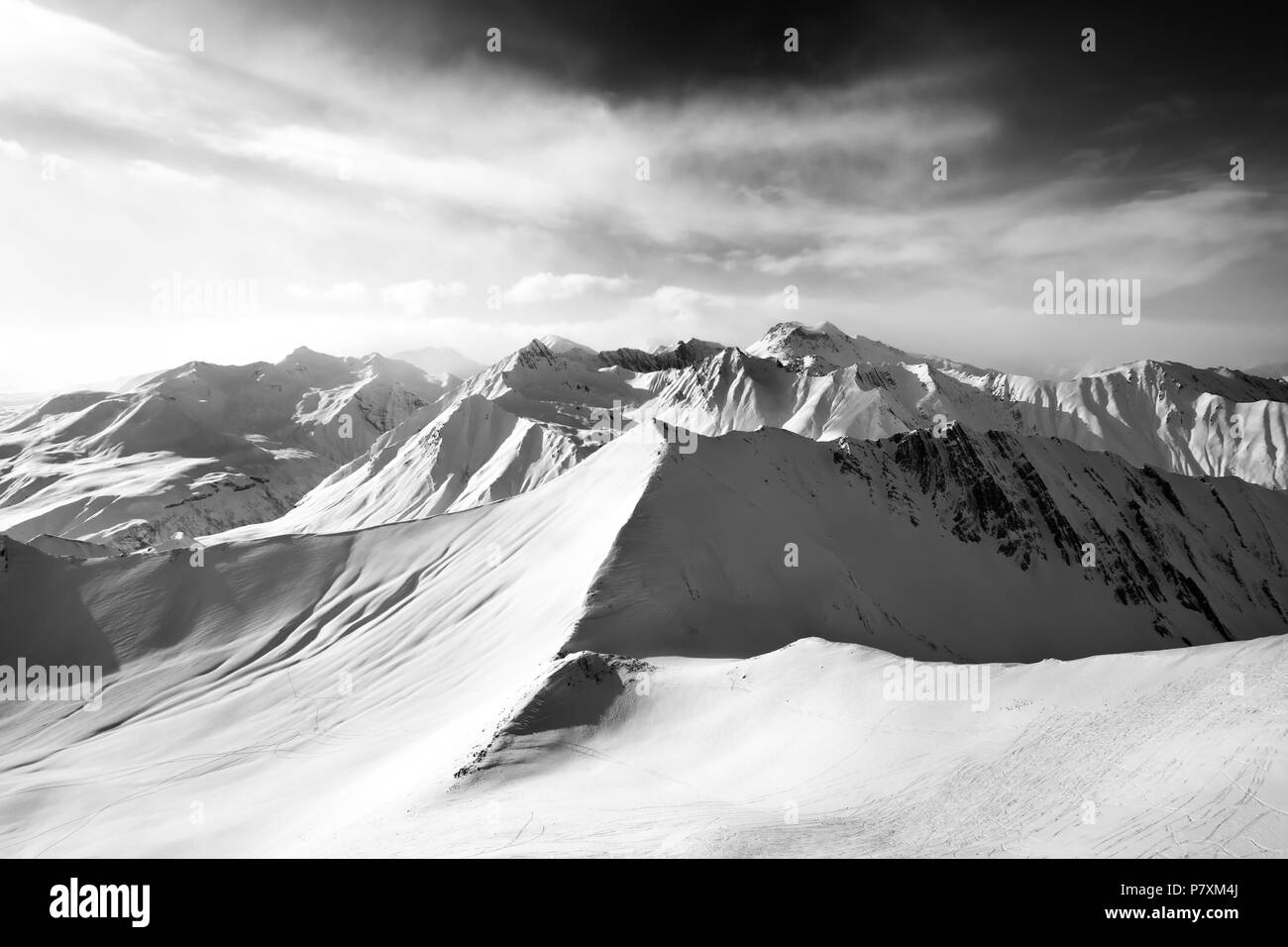 Black and white snowy off-piste slope and sunlight sky. Caucasus Mountains, Georgia, region Gudauri in winter. Wide angle view. - Stock Image