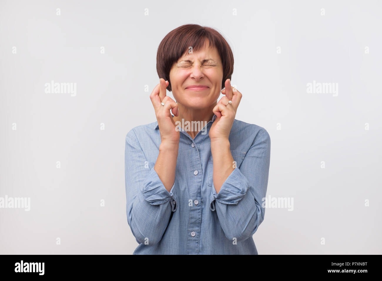 Studio portrait of attractive mature woman having excited, superstitious and naive look, keeping fingers crossed - Stock Image