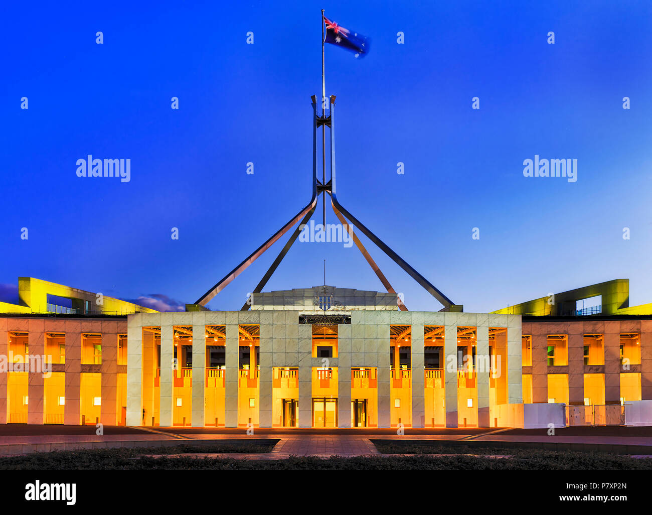 Facade and national flag on tall flagpole over modern acting australian parlament in Canberra capital city with bright illumination at sunset against  - Stock Image
