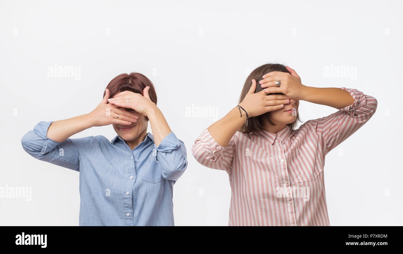 Two european women mother and daughter covering their faces using hands. - Stock Image