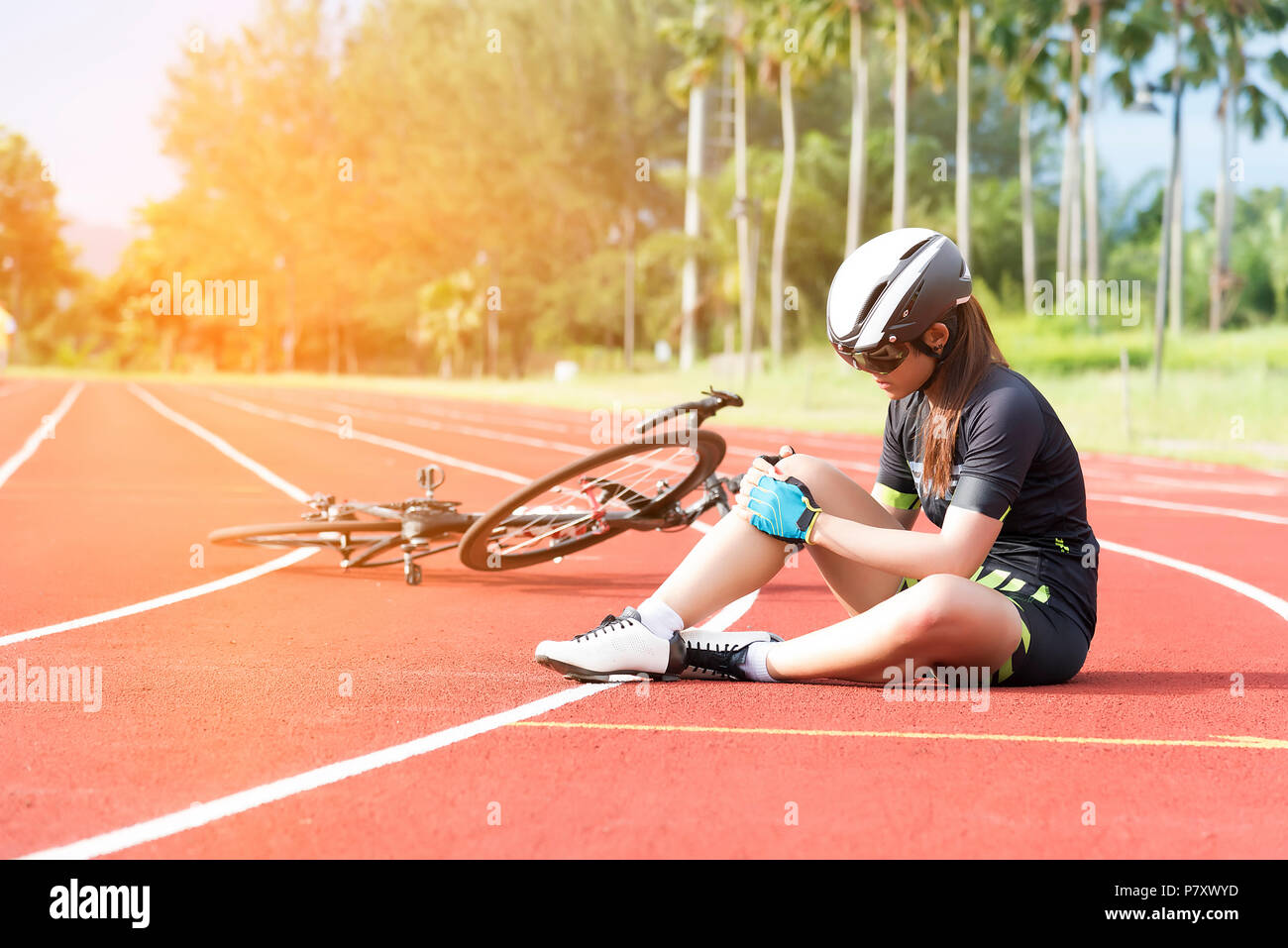 Girl has sport accident injur at her knee from bicycle, Sport and Accident concept - Stock Image