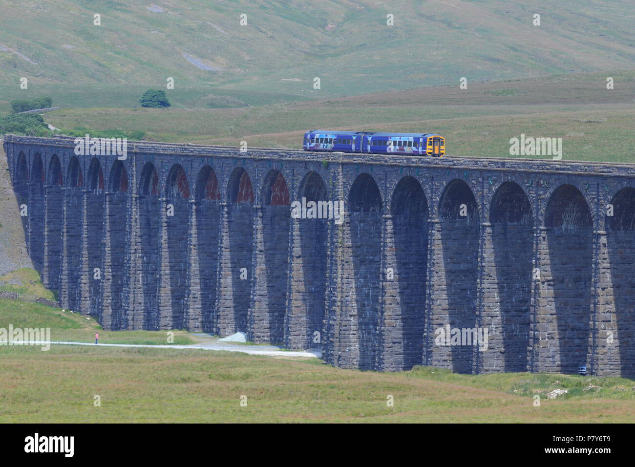 A Northern Rail train crosses over the impressive Ribblehead Viaduct built by the victorians back in 1975 - Stock Image