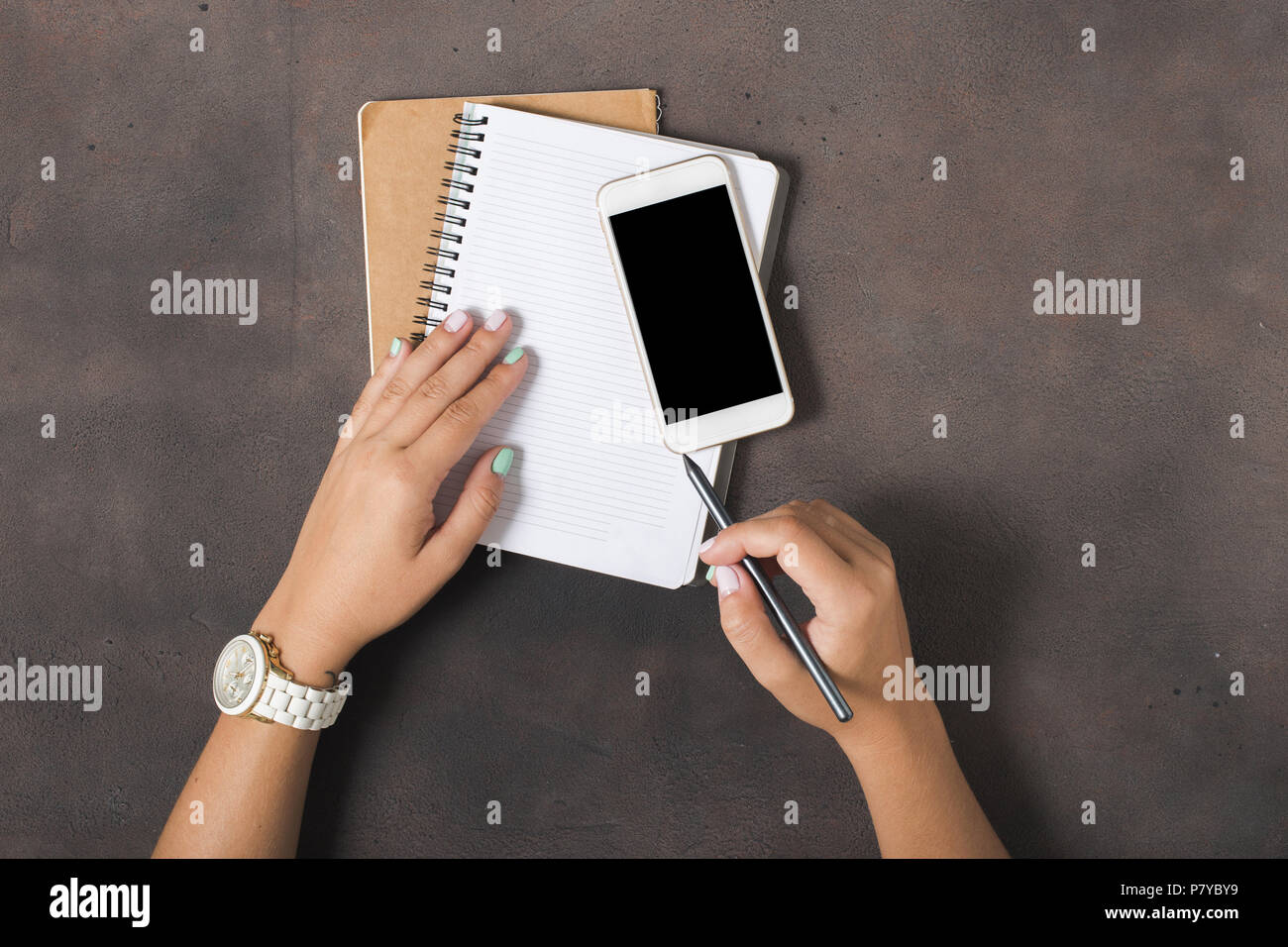 Women write in a notebook in the workplace. Flat lay, top view. Concept feminine working place - Stock Image