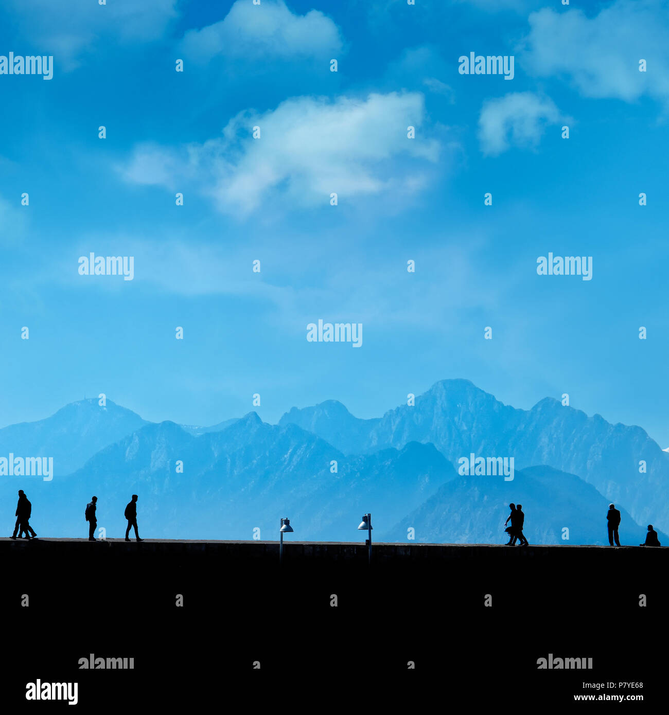 Silhouetted  people relaxing on street over blue sky and high mountains - Stock Image