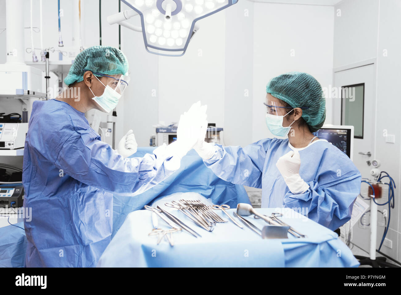 Doctors and nurse do hi five after succeeding from surgery in operation room. Healthcare and Hospital concept - Stock Image