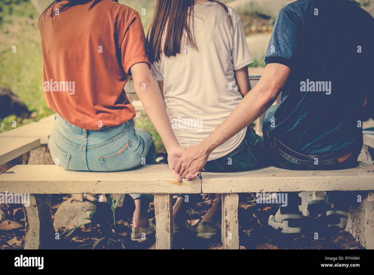 Boyfriend and another woman grab hands from behind together without sight of his girlfriend. Paramour and divorce concept. Social problem and cheating - Stock Image
