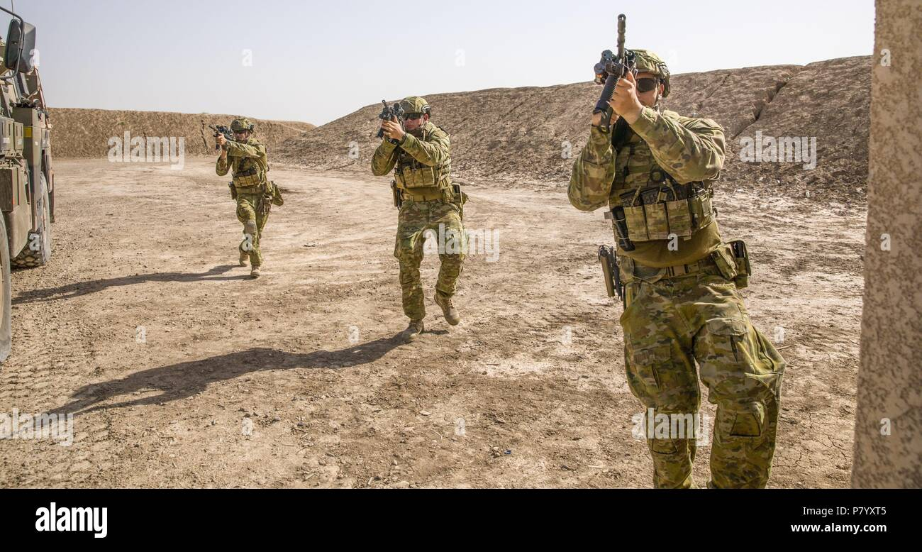 Australian soldiers, with Task Group Taji's quick reaction force, demonstrate building clearance drills during concurrency training with U.S. Soldiers of Bandit Troop, 3rd Calvary Regiment at Camp Taji, Iraq, June 11, 2018. A Coalition created from a diverse international community will continue its support to the people of Iraq in order to enhance the capabilities of the nation to ensure security and stability. (U.S. Army photo by Spc. Audrey Ward) - Stock Image