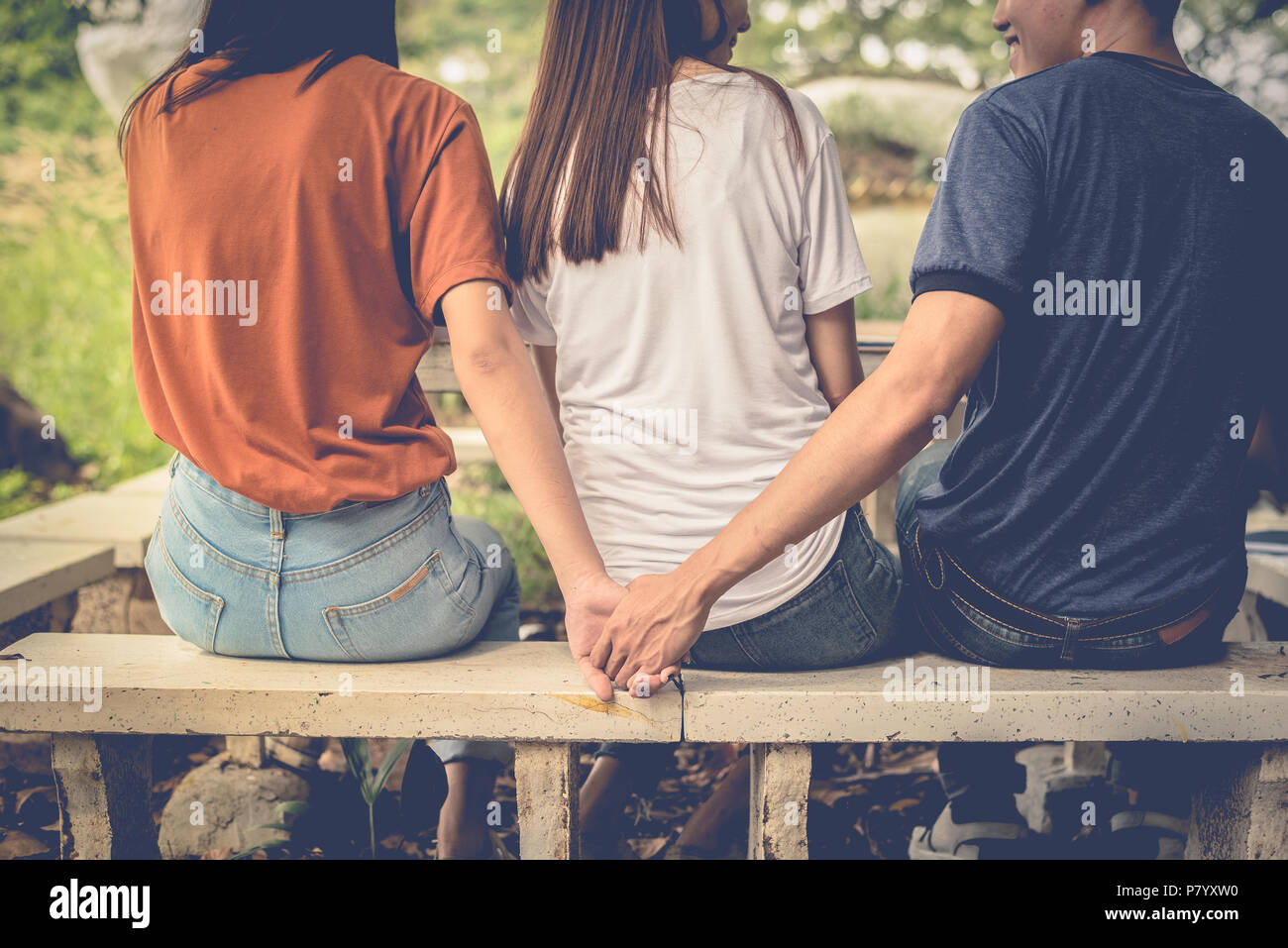 Boyfriend and another woman grab hands from behind together without sight of his girlfriend.. Paramour and divorce concept. Social problem and cheatin - Stock Image