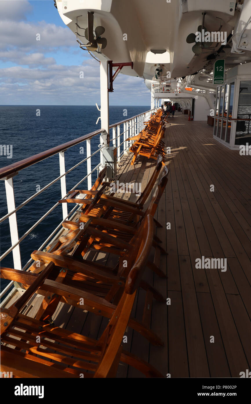 Deck Chairs Facing Out To Sea On Teak Deck In Sunlight On Deck 7 Of The  Queen Mary 2 On An Early Spring Crossing Of Atlantic Ocean; Horizon And  Clouds.