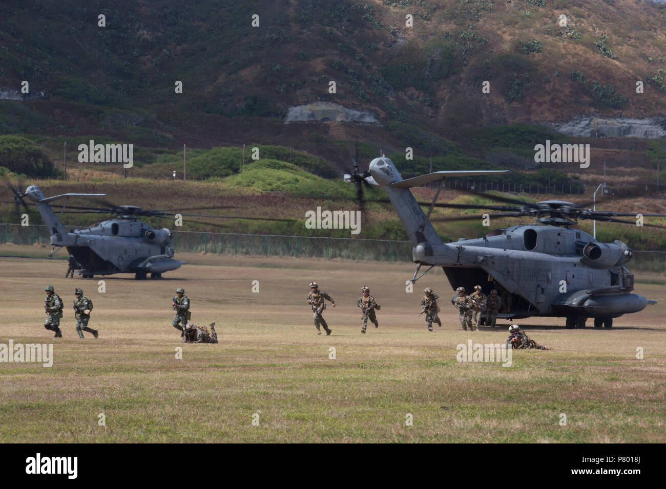180706-M-KC456-1114 MARINE CORPS BASE HAWAII (July 6, 2018)  Philippine and U.S. Marines with Company A, 1st Battalion, 3rd Marine Regiment, disembark from a CH-53 Super Stallion helicopter and post security during an air-assault rehearsal as part of Rim of the Pacific (RIMPAC) exercise on Marine Corps Base Hawaii July 6, 2018. RIMPAC provides high-value training for task-organized, highly-capable Marine Air-Ground Task Force and enhances the critical crisis response capability of U.S. Marines in the Pacific. Twenty-five nations, 46 ships, five submarines, about 200 aircraft and 25,000 personn - Stock Image