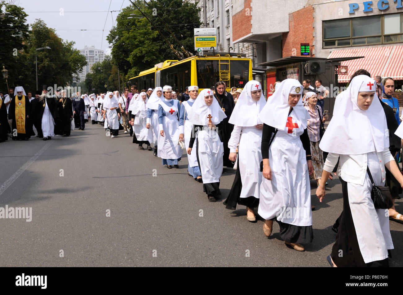 Orthodox sisters of charity dressed in white cassocks with red cross signs going down street. the Day of Baptism of Rus. July 27, 2017. Kiev, Ukraine - Stock Image