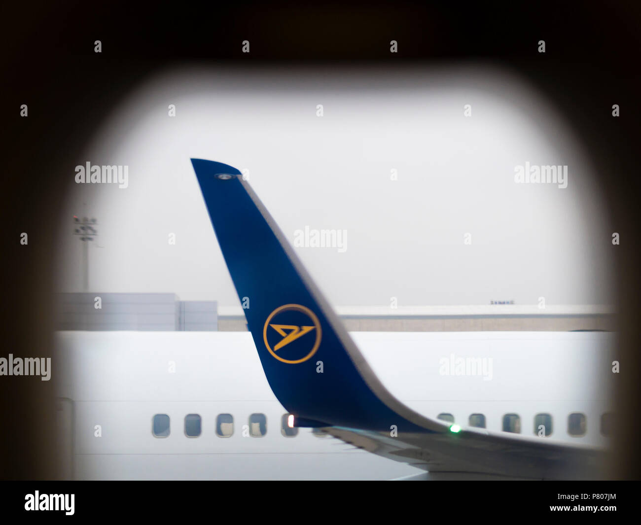 Winglet of a Boeing 767-300ER aircraft of German airline Condor, seen through the window of an aircraft parked nearby. - Stock Image