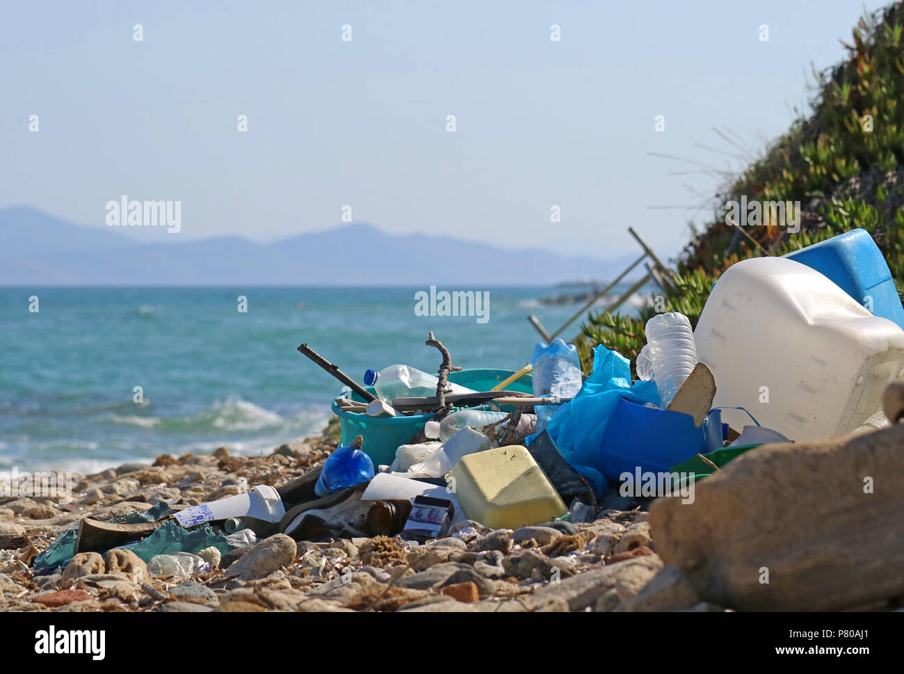 plastic garbage and wastes on the beach with the sea and an island on background Stock Photo