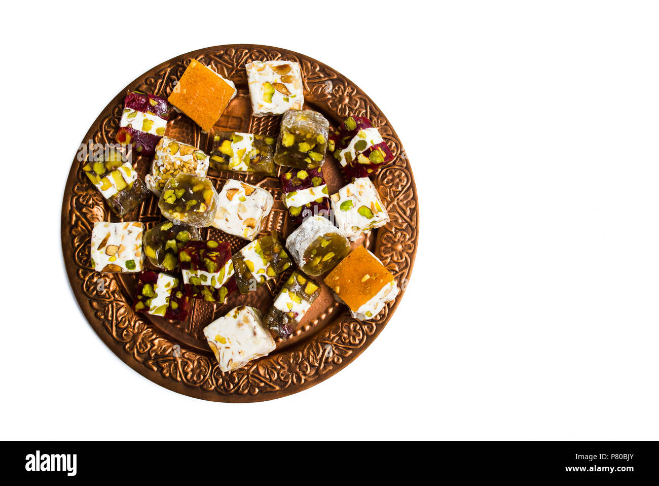 Various Turkish delights on a copper plate isolated on white - Stock Image