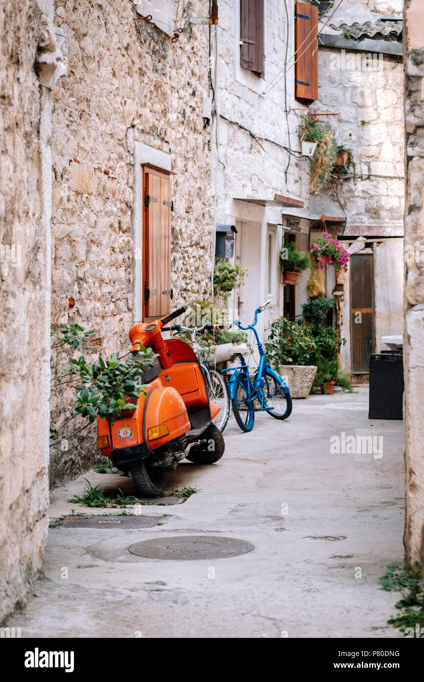 Scooter and bicycle in an idyllic mediterranean backstreet - Stock Image
