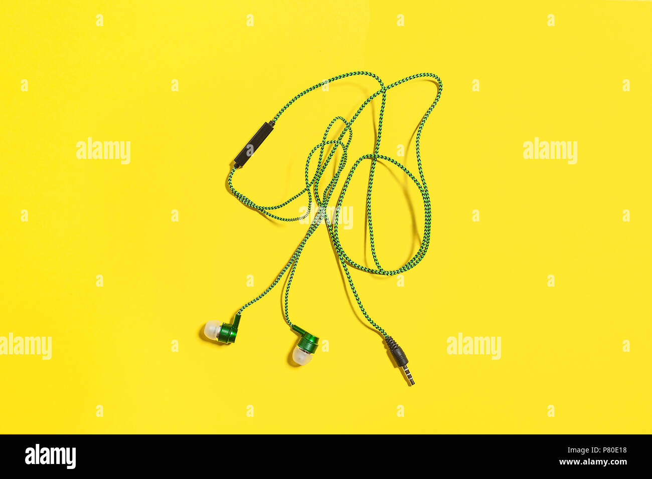 green earphones on a yellow background - Stock Image