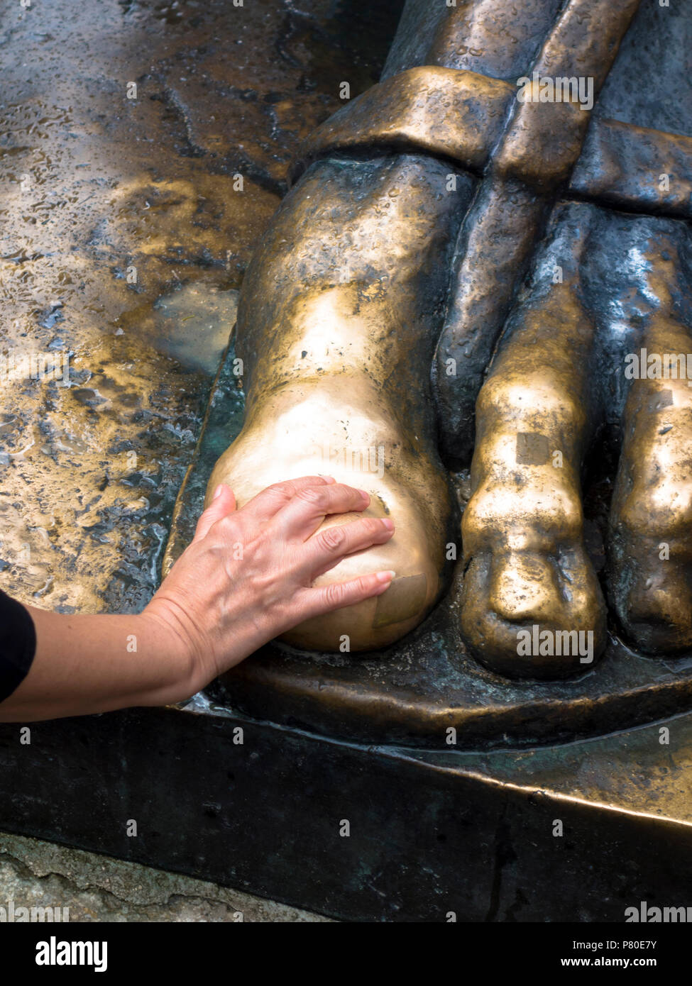 Visitor touching the feet of the statue of Gregory of Nin by Ivan Meštrovic in Split, Croatia. Touching the statue's feet is said to bring good luck. Stock Photo