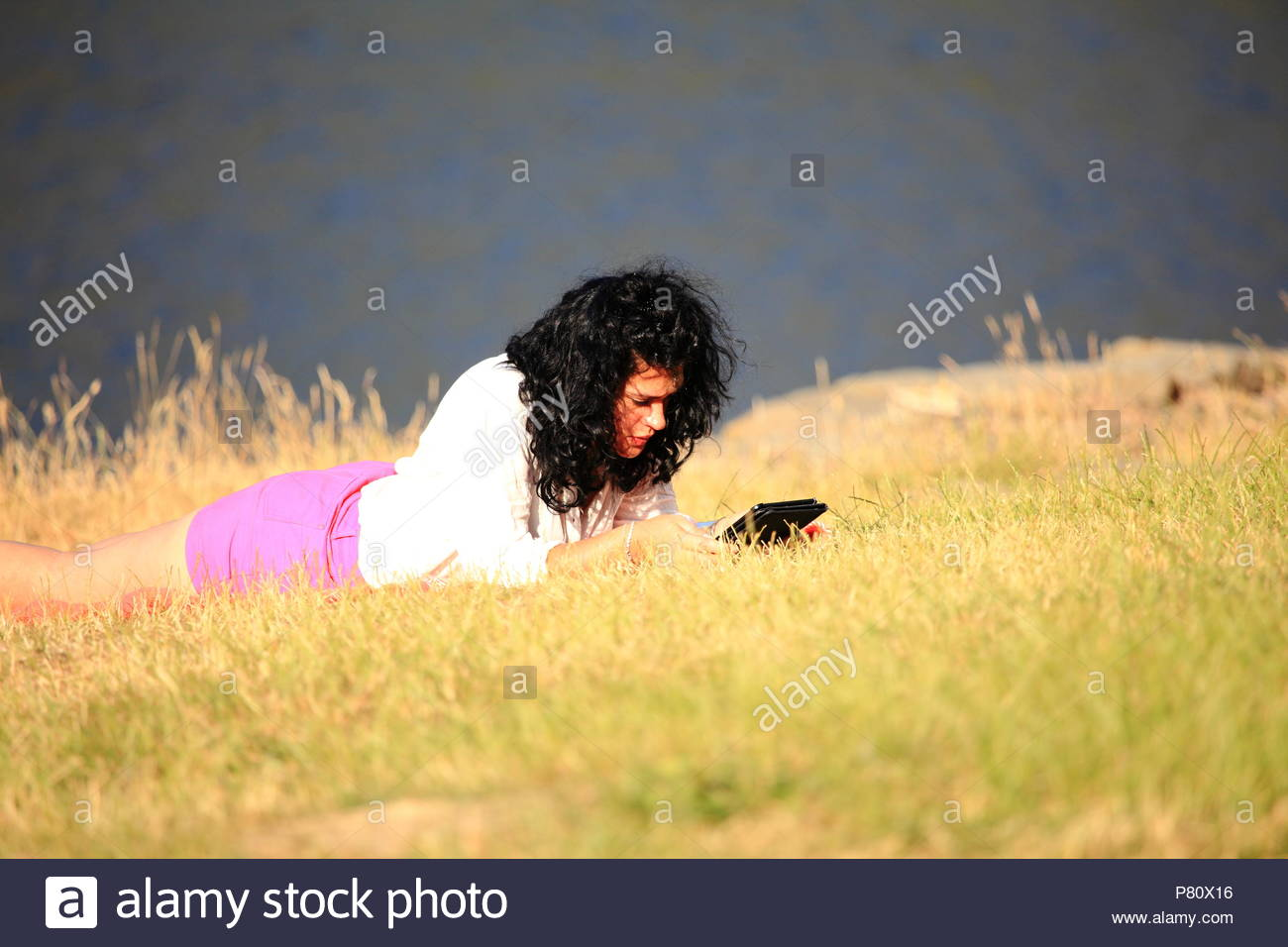 A woman in pink shorts lying on the grass in the summer sun with her tablet. Dove Stone Reservoir Oldham Greenfield Saddleworth summer July 2018 - Stock Image
