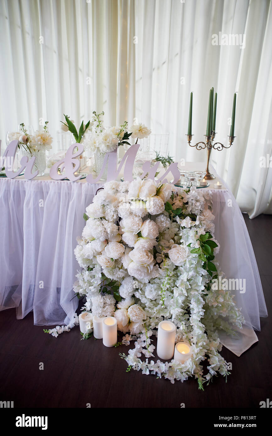 Flower garland of pine-shaped roses hangs from the table. Wedding decoration, floristry. Candelabra with green candles.The inscription Mr. and Mrs.. Drape the table with chiffon - Stock Image