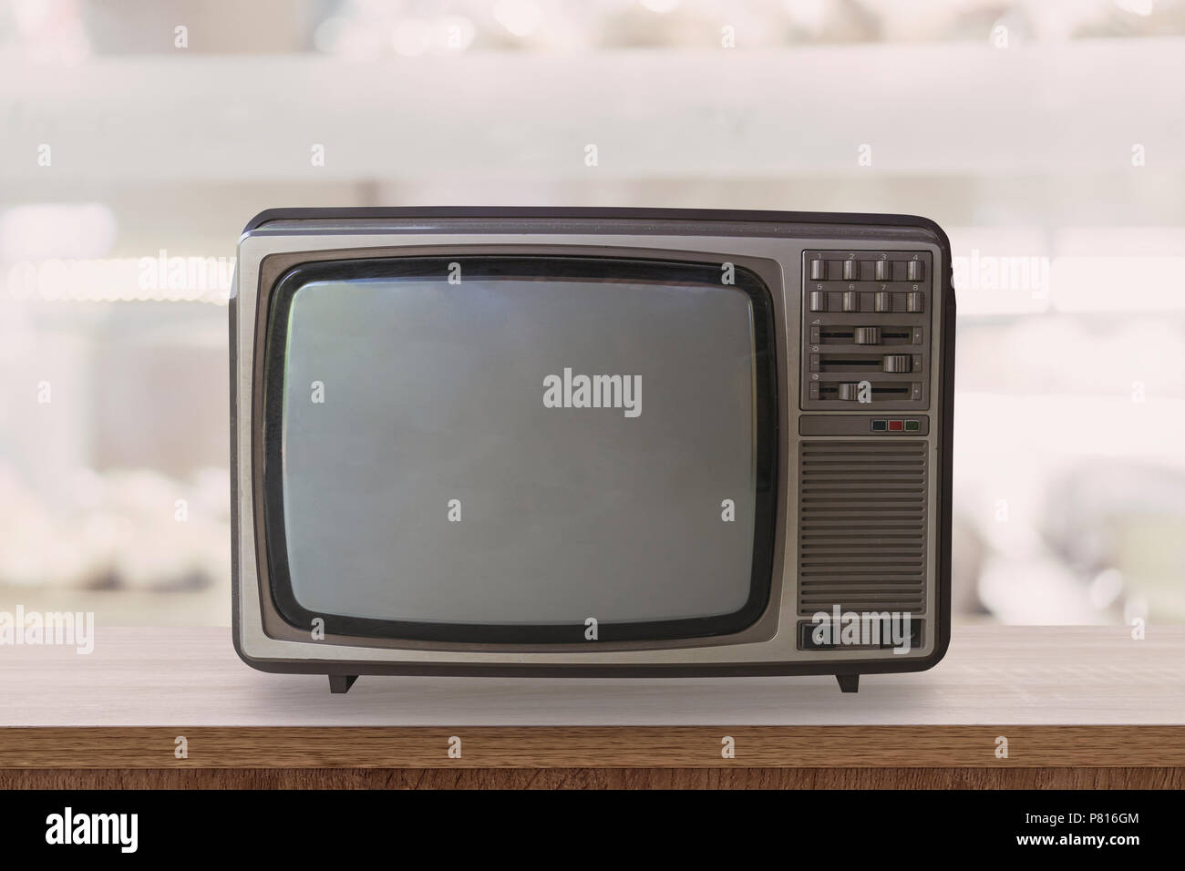 Vintage TV box on wooden table with blur background. - Stock Image