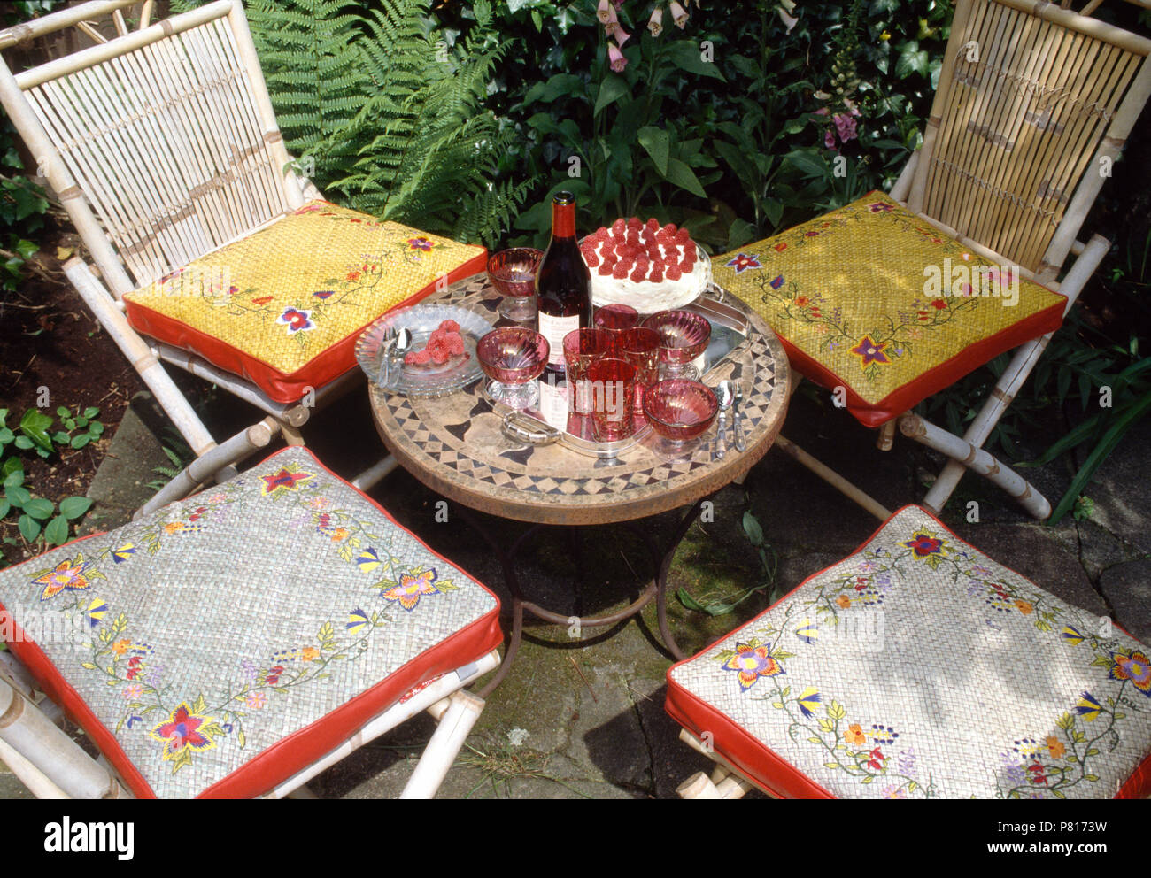 Floral Tapestry Box Cushions On White Bamboo Chairs On Patio With Cranberry  Glass On Small Mosaic Table